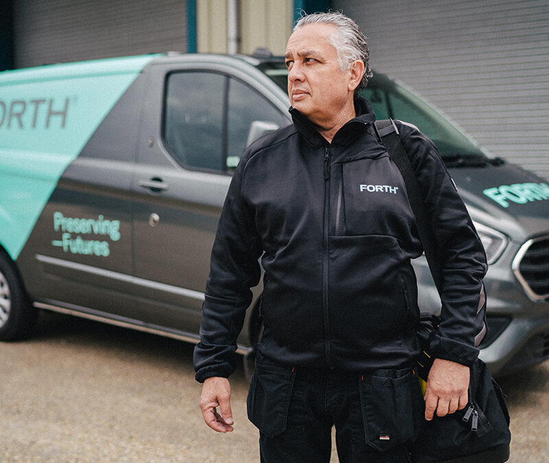 A FORTH® engineer holding an equipment bag stands in front of his van bearing the FORTH® livery.