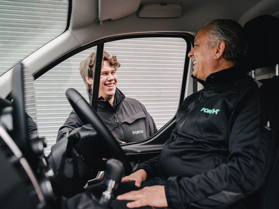 A photograph of two FORTH® engineers, one inside a van, one outside, sharing a joke
