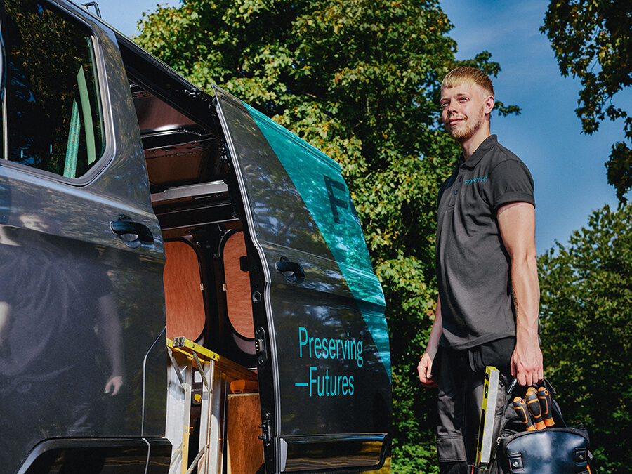 A young FORTH® engineer carrying his tools stands proudly next to his van.