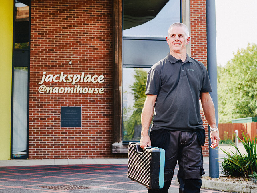 A FORTH® engineer carrying a tool box stands in front of jacksplace, a Naomihouse building.